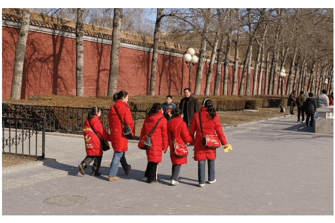imagen de mujeres y niñas asiáticas que visten abrigos rojos y caminan en la calle