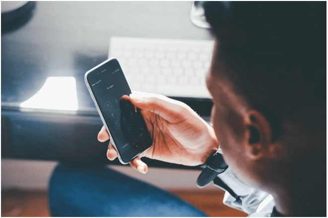 imagen de hombre que sostiene con su mano un móvil con la pantalla de fondo oscuro