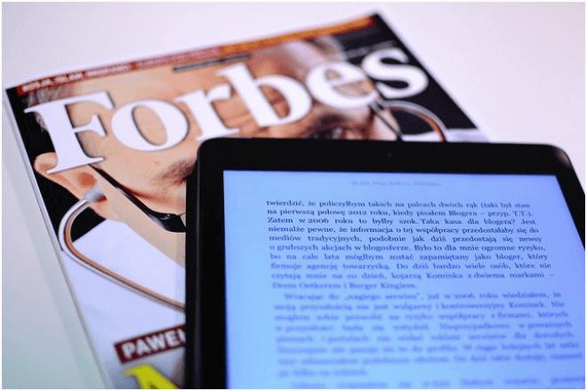 imagen de una tablet con un texto en pantalla y debajo una revista Forbes
