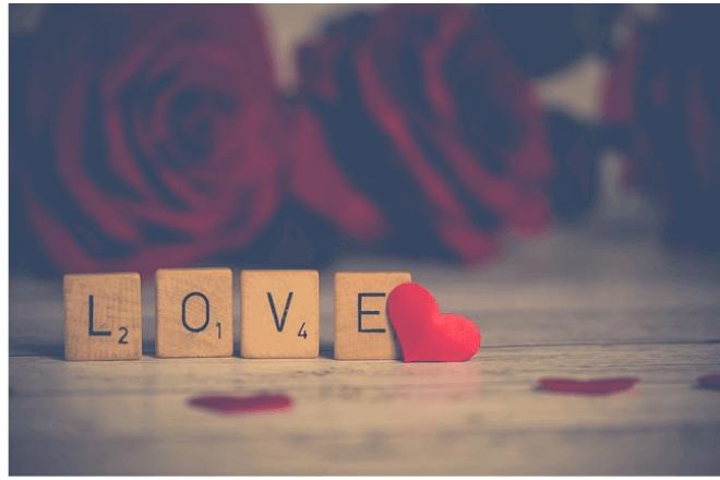 foto de letras sobre madera que dicen LOVE con un corazòn y rosas al fondo