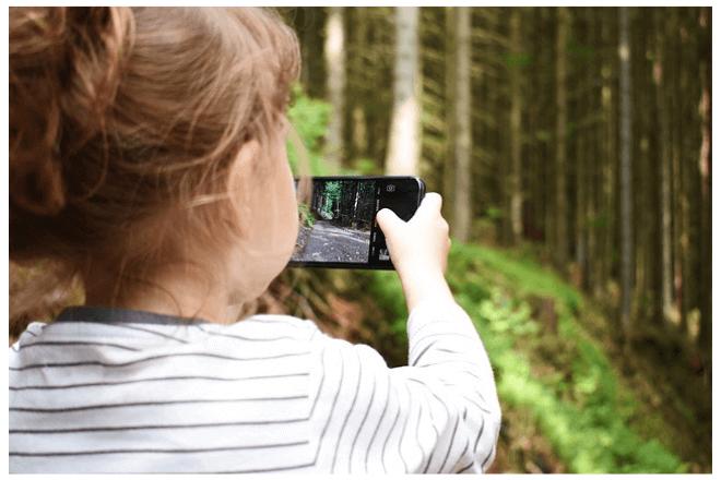 foto de niña de espaldas que toma una fotografía con un móvil