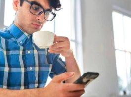 Hombre joven con lentes mira su móvil mientras toma café