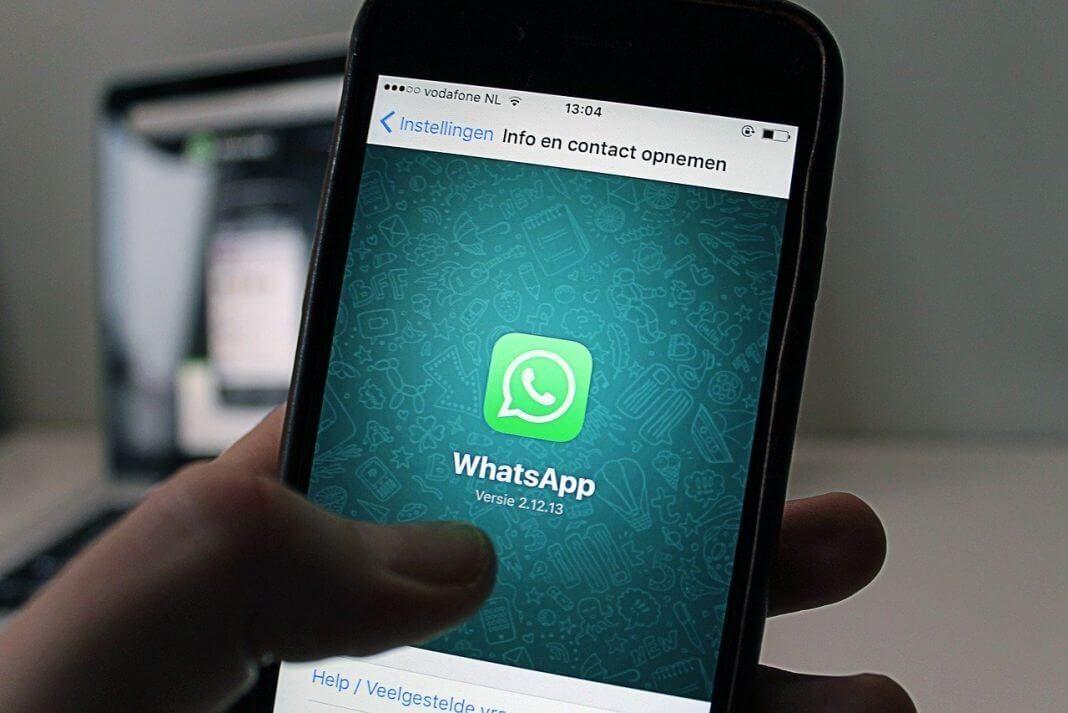Persona con un smartphone en la mano y en la pantalla el logo de whatsapp