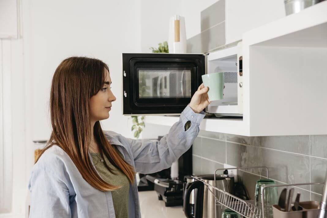 Mujer joven usando un microondas para encimeras