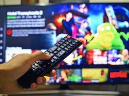 Fotografía de un joven que tiene un control remoto en la mano y en el fondo un televisor con imágenes