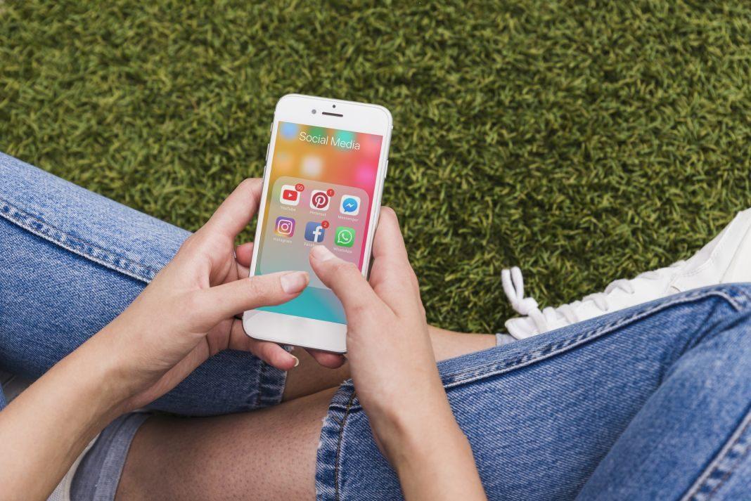 Mujer sosteniendo teléfono móvil con la aplicación de WhatsApp