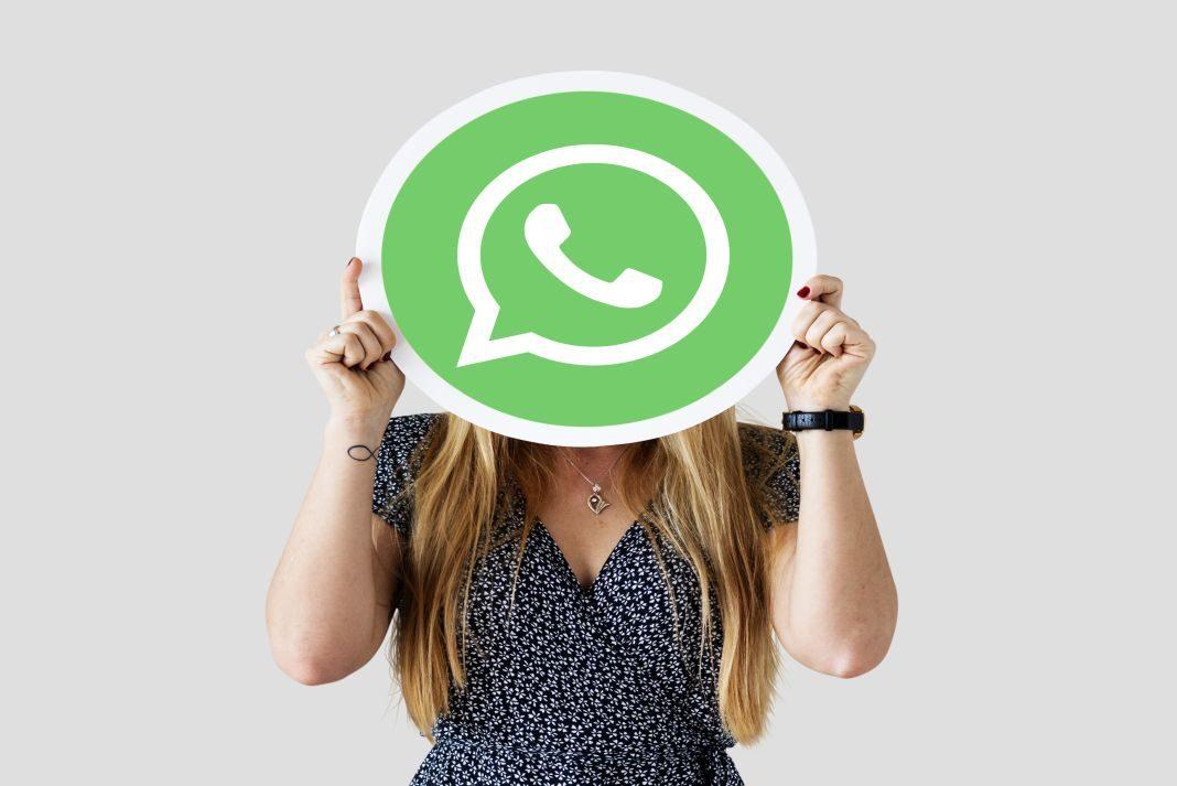 Mujer mostrando un ícono de WhatsApp