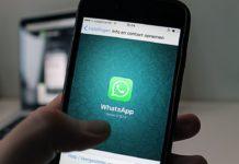 Hombre tiene móvil en la mano con el logo de Whatsapp