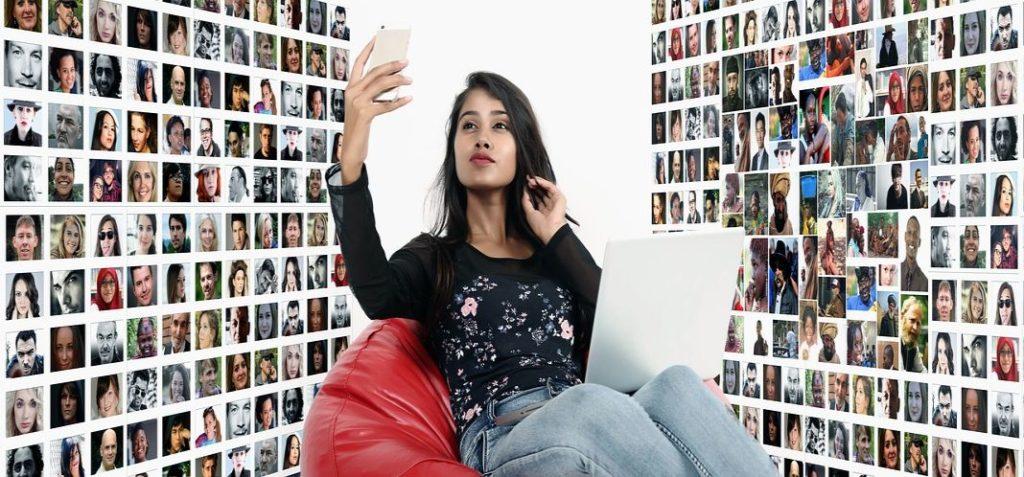 Mujer joven toma una fotografía con su móvil teniendo de fondo muros llenos de fotografias