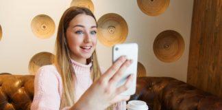 Joven sonriente con smartphone en la mano