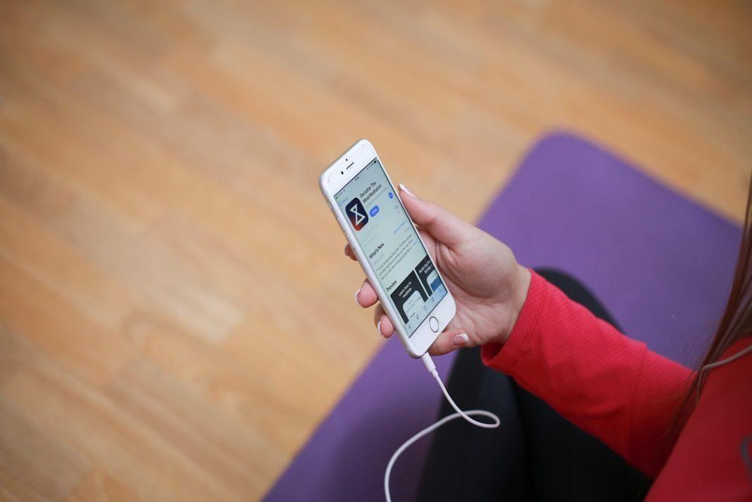 Mujer sentada sobre tapete de yoga con un móvil en la mano