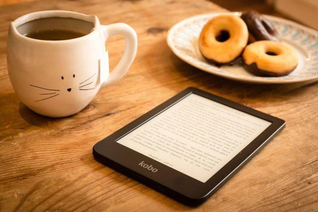Una taza de chocolate, donas y un libro electrónico