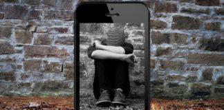 Imagen de un joven cubriendo su cara mostrada a través de un móvil