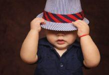 Bebé cubriendose la cara con un sombrero