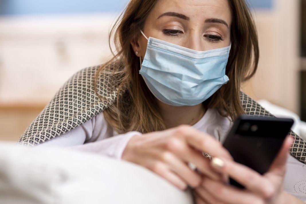 Mujer con tapabocas mira su teléfono