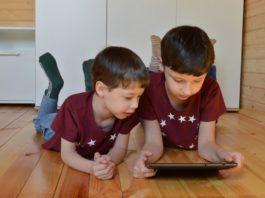 Niños acostados en el piso mirando una tablet