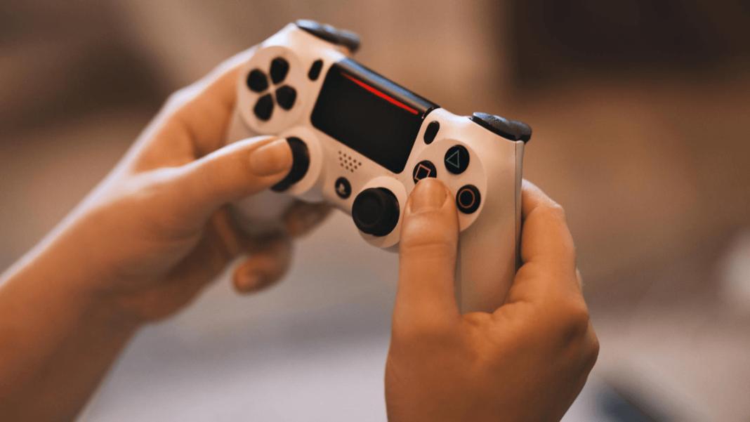 manos de un joven sostienen un control de videojuegos
